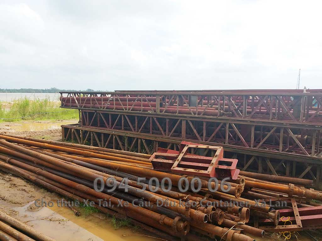 (Ảnh: Dự án vận chuyển thiết bị vật tư công trình Nhà Máy Nhiệt Điện Nam Sông Hậu - Hậu Giang; Ảnh được chụp lại cảnh kho bãi chứa vật tư chuẩn bị di dời)