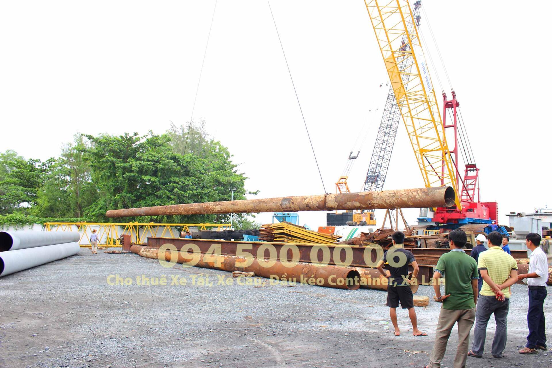 (Ảnh: Dự Án vận chuyển Búa Đóng Cọc Thủy Lực từ Sài Gòn đi Hà Nội; trong ảnh là cảnh xe cẩu đang đưa Phụ kiện của cây búa đóng cọc thủy lực lên xe đầu kéo container thùng mui bạc dài 14.2m)